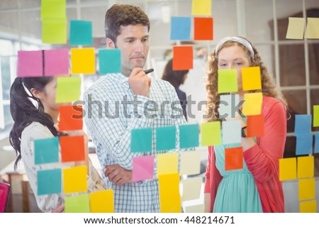 Casual colleagues looking at sticky notes on wall in the office