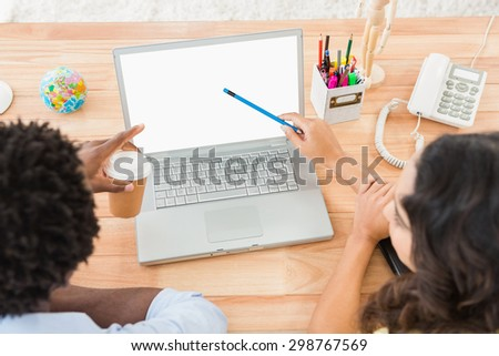 Casual colleagues working together and using laptop in the office - stock photo