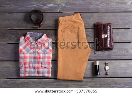 Casual collection of men's clothing. Clothing and accessories on a wooden background. - stock photo
