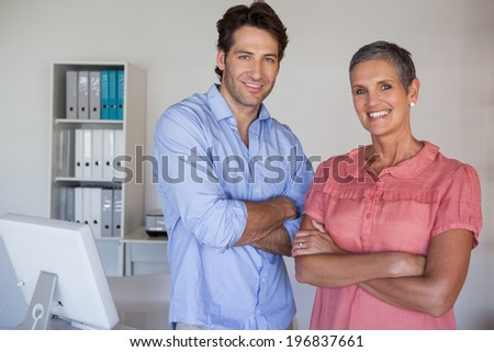 Casual confident business team smiling at camera in the office - stock photo