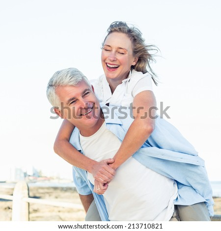 Casual couple having fun by the sea on a sunny day - stock photo