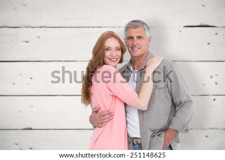 Casual couple hugging and smiling against white wood - stock photo