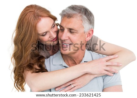 Casual couple hugging and smiling on white background - stock photo