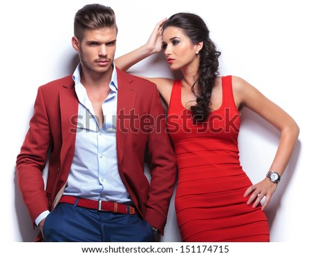casual couple leaning against a white wall, man with hands in his pockets looking at the camera . woman looking at the man while leaning on his shoulder - stock photo
