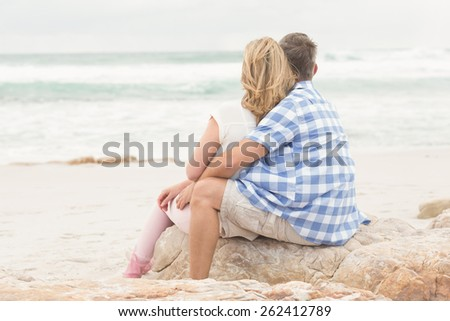 Casual couple looking to sea at the beach - stock photo