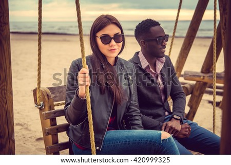 Casual couple sits on swing. Afro american guy and caucasian female on a beach - stock photo