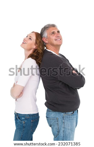 Casual couple smiling and looking up on white background