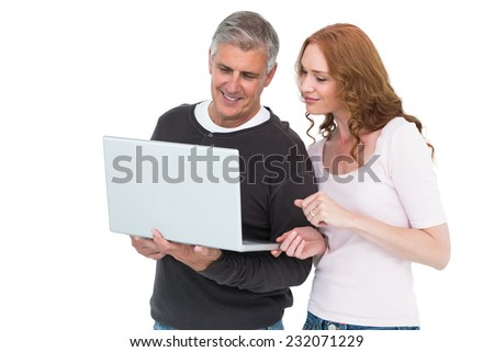 Casual couple using laptop together on white background