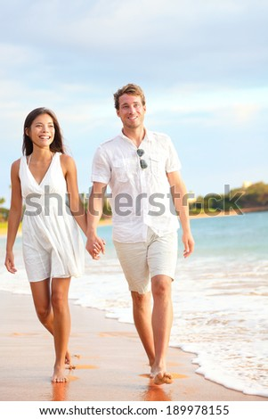 Casual couple walking on beach holding hands on honeymoon travel vacation holidays. Young multi-ethnic couple lovers, Asian woman and Caucasian man. - stock photo