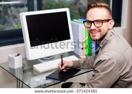 Casual designer using graphic designer in the office - stock photo