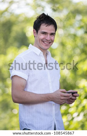 Casual Dressed Young Man Texting on Cell Phone Outdoor Smiling