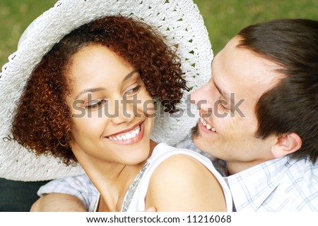 Casual, easy and breezy young couple relaxing and cuddling in the park - stock photo