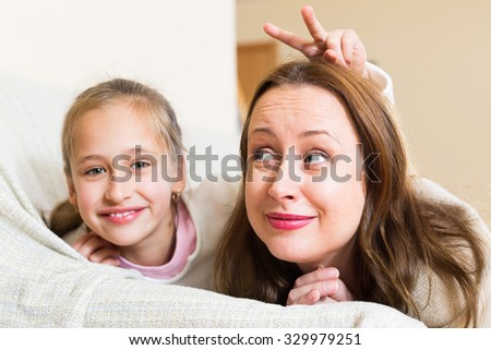 Casual family portrait of cheerful mother with smiling daughter. Focus on woman