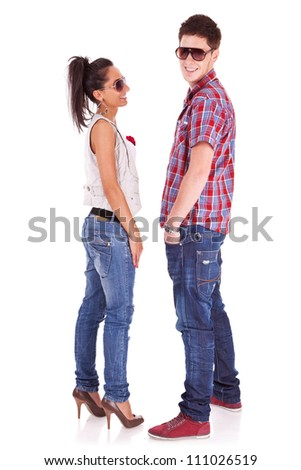 casual fashion couple wearing sunglasses on a white background . The boy is holding his hands in his pockets and the girl is looking at him and smiling - stock photo