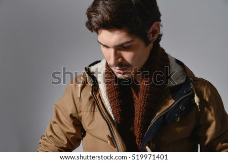 casual fashion man pulling his jacket posing in studio