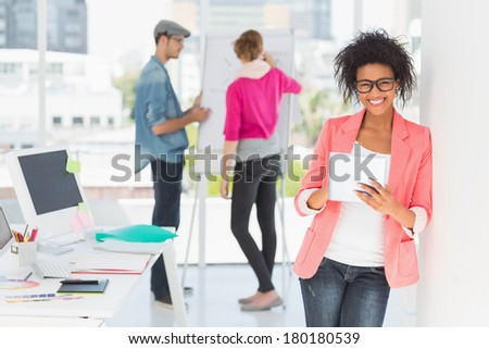 Casual female artist using digital tablet with colleagues in the background at a bright office - stock photo