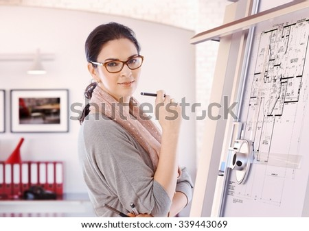 Casual female caucasian architect standing at drawing board and floor plan with pencil in hand at office. Wearing glasses, smiling, looking at camera. - stock photo