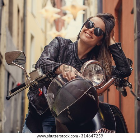 Casual female on moto scooter on the street in old town. - stock photo