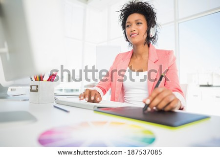 Casual female photo editor using graphics tablet in a bright office - stock photo