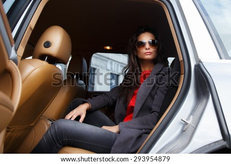 Casual female with long black hair in sunglasses sitting in the car on back seats. - stock photo
