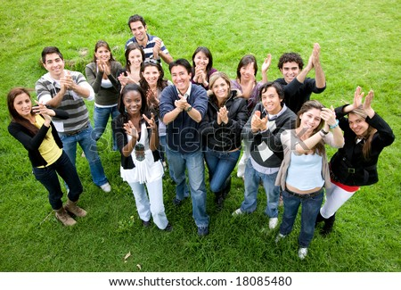 casual friends smiling and clapping upwards in the park - stock photo