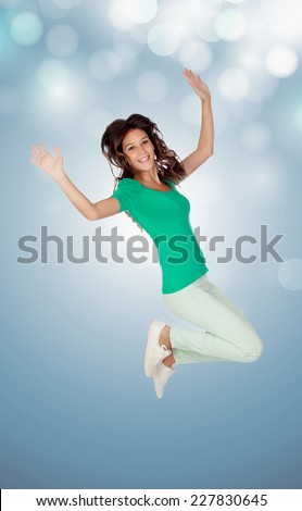Casual girl jumping on a blue and sparkly background - stock photo