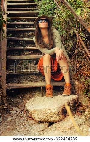 Casual girl wearing long orange skirt sitting on the old wooden stairs outdoor. - stock photo