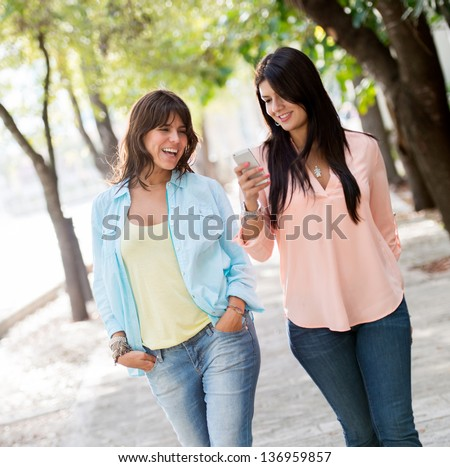 Casual girls walking outdoors using a mobile phone