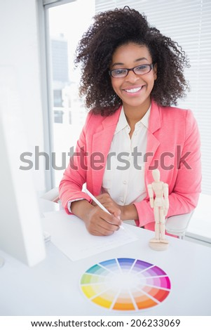 Casual graphic designer working at her desk sketching in her office - stock photo