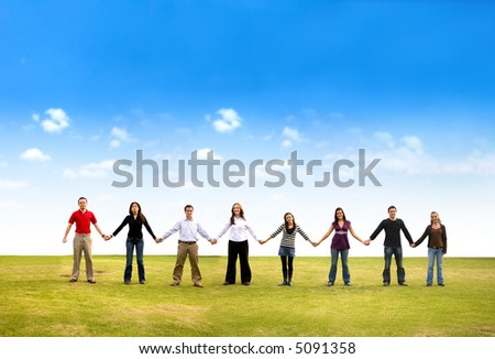 Casual group of friends holding hands outdoors in a park on a beautiful day - stock photo