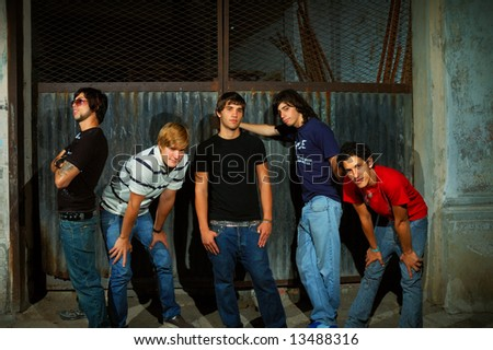 Casual group of teenagers standing against grunge wall - stock photo