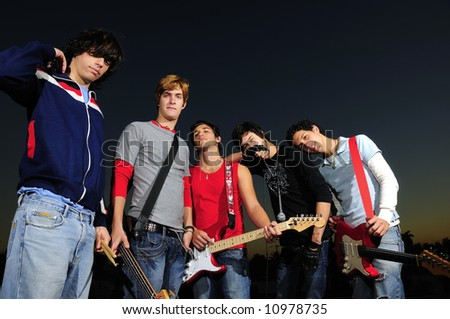 Casual group of young musicians posing with instruments - stock photo