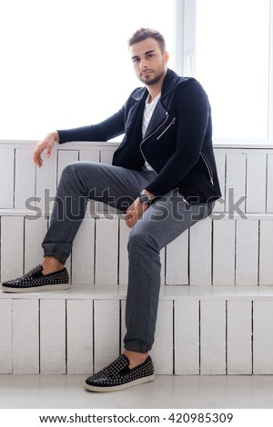 Casual guy posing on white wooden steps.