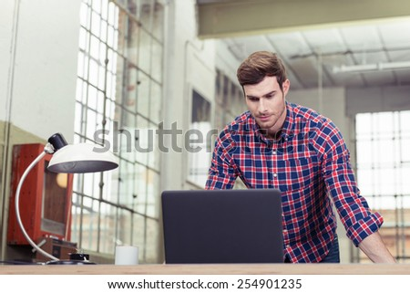 Casual handsome young businessman standing reading his laptop computer screen with a serious expression in a bright office with large windows, low angle view - stock photo