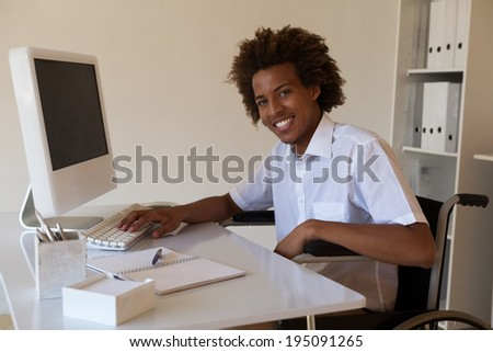 Casual happy businessman in wheelchair working at his desk in his office - stock photo