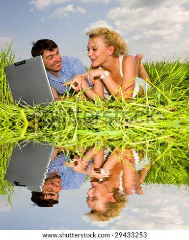 Casual happy couple on a laptop computer outdoors. Lay on the green grass - stock photo