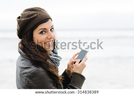 Casual happy woman texting message or email on smartphone outside. Female brunette using cellphone for internet browsing. - stock photo