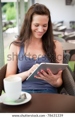Casual happy young woman using her tablet in an open air cafe - stock photo