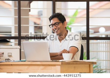 casual indian man smiling and working at office - stock photo