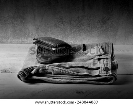 Casual jeans and leather wallet and pouch over grunge still life style black and white version - stock photo