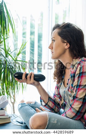 casual lady watching TV while sitting and relaxing on sofa - stock photo