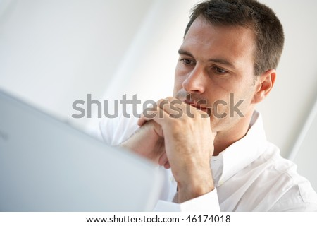 casual looking businessman working on laptop computer - stock photo