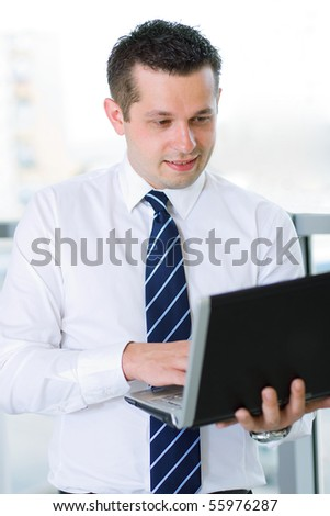 Casual looking businessman working on laptop computer in front of office window.