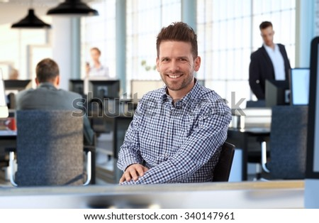 Casual man at sitting at desk in office smiling. - stock photo