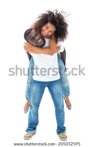 Casual man giving his smiling girlfriend a piggy back on white background - stock photo
