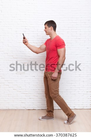 Casual Man Going Using Cell Phone Smartphone Social Network Communication Full Length Over White Brick Wall - stock photo