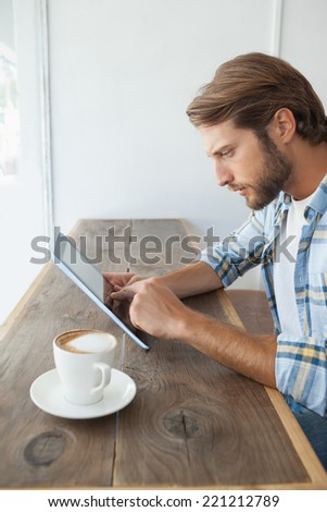Casual man having a coffee using tablet at the coffee shop - stock photo