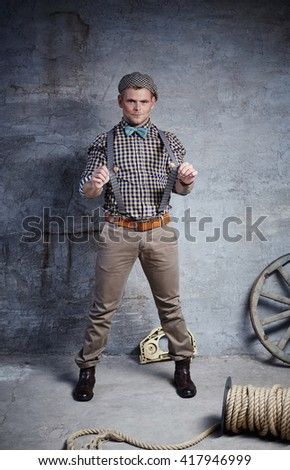Casual man in a bow tie posing in a studio. - stock photo