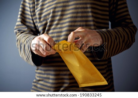 Casual man is opening yellow document postal envelope - stock photo