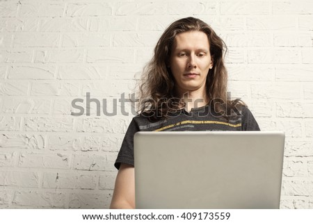 Casual Man IT Programmer with Laptop computer near White brick Wall - stock photo